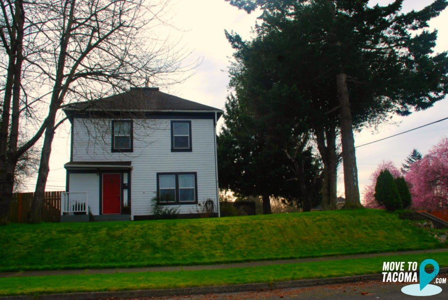 Beige house with red door in Central Tacoma, WA.