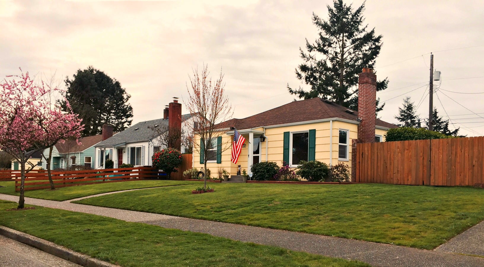 Yellow house with green shutters and an american flag in central tacoma WA