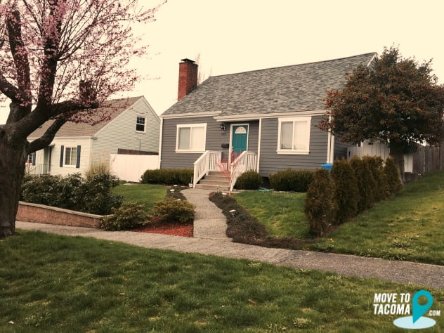 Grey house with teal door and cherry blossom tree in Tacoma WA