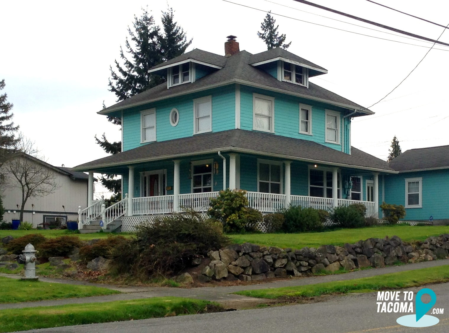 Teal house with wraparound porch in Tacoma's eastside neighborhood
